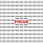 "Text ""focus"" in red on background of lines with blurred black text ""focus"""