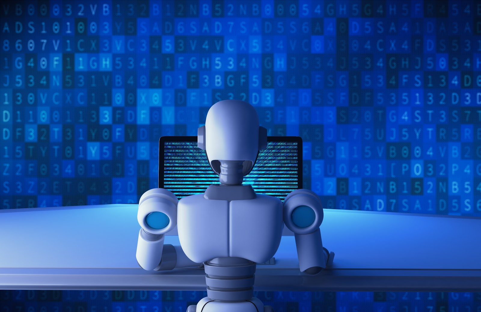 Robot with back to viewer sitting in front of computer screen